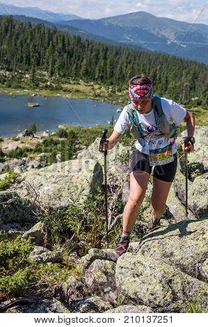 ERGAKI, RUSSIA - AUGUST 05 2017: Unknown girl sportswoman running through the mountains, participant in the trailrunning contest SKAYRANFEST August 5, 2017 in the national park Ergaki, Russia