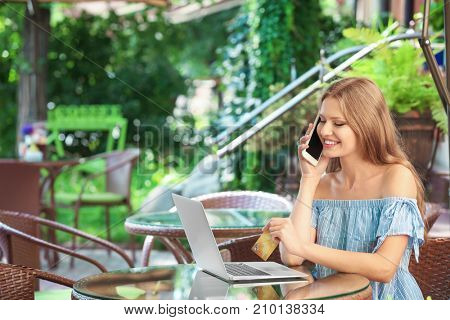 Young woman with cell phone, laptop and credit card in cafe