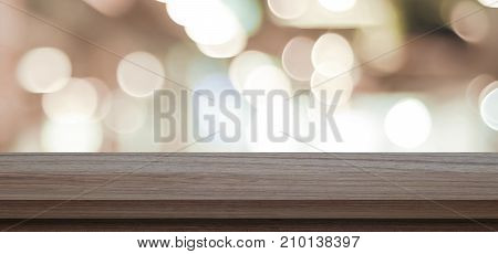 Empty wooden table over blur store background product and food display montage background