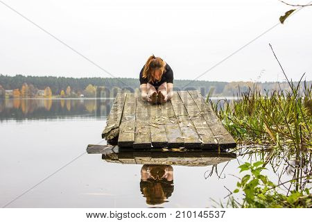 Girl with a sports sexy figure is engaged in sports yoga stretching fitness on background of a calm autumn river lake. Girl is reflected in water. Meditation relaxation balance calmness.