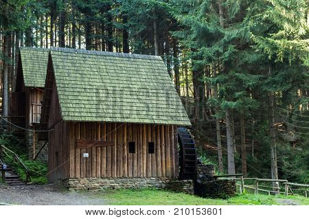 Western style pioneer frontier water mill wheel wooden building in the forest