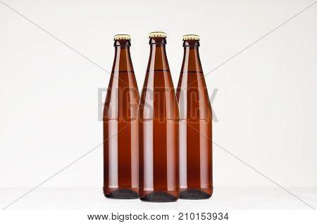 Group brown NRW beer bottles 500ml mock up. Template for advertising design branding identity on white wood table.