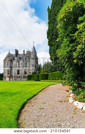 Pathway leading along side of large green lawn and tall trees to beautiful old castle