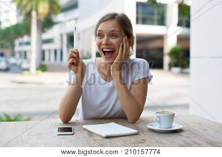 Closeup portrait of cheerful young beautiful woman working, raising pen and having excellent idea at cafe table outdoors with street view in background. Front view.