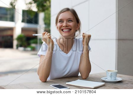 Closeup portrait of cheerful young beautiful woman working, pumping fists and having excellent idea at cafe table outdoors with street view in background. Front view.