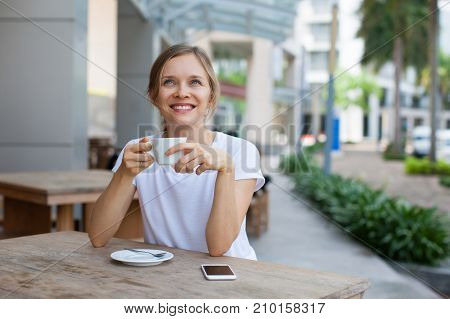 Closeup portrait of smiling young beautiful woman looking away and drinking coffee at cafe table outdoors with street view in background. Front view.