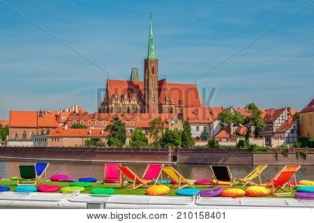 Wroclaw/Poland- August 18, 2017: View of Church of Holy Cross and St. Bartholomew on Tumski Island and Odra river through touristic boat deck with colorful chairs and pillows for sunbathing and relaxation