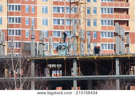Construction of multi-storey monolithic house and workman builder on background of freshly built multi-storey residential building