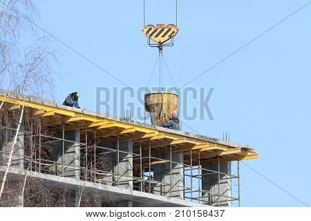 Construction of multi-storey monolithic house and workers builders on background of blue sky
