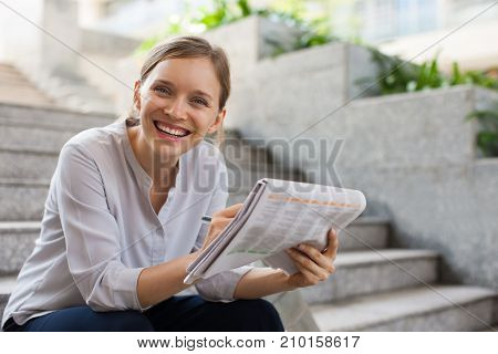 Closeup portrait of smiling young beautiful woman looking at camera, reading newspaper and sitting on stairs outdoors