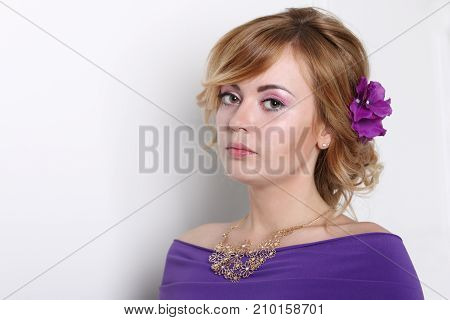 Beautiful young blonde woman in purple dress with clean skin and make-up on grey background