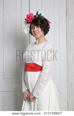 Beautiful young brunette woman in white dress with flower wreath in her hair standing against white doors in photo studio cropped