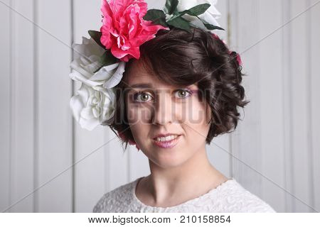 young brunette woman with clean skin make-up and flower wreath in her hair posing near white door portrait in front