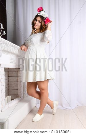 beautiful pregnant woman in white dress and wreath in her hair is standing near fireplace