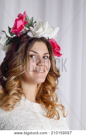 portrait of beautiful woman in white dress and flower wreath in her hair