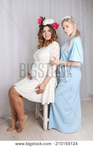 two beautiful girls in dresses with flowers in her hair in studio one is sitting other is standing