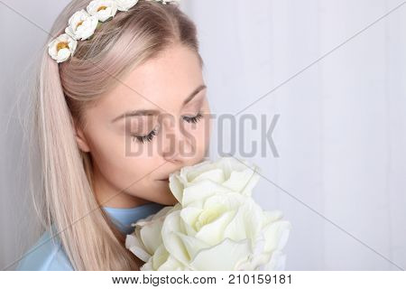 Beautiful young blonde woman with clean skin and flower wreath in her hair smelling bouquet white rose eyes closed