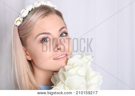 Beautiful young blonde woman with clean skin and flower wreath in her hair holding bouquet white rose closeup