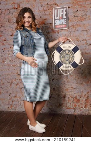 beautiful pregnant woman in striped dress jacket is standing near brick wall in studio in hands of life buoy