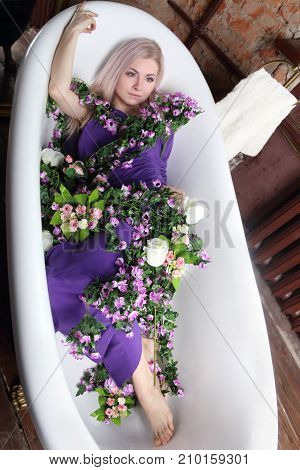 beautiful girl in lilac dress lies in bath with flowers in photo studio