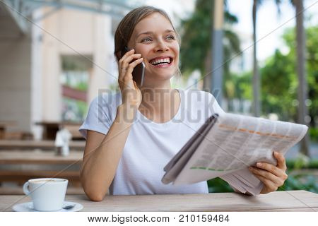 Closeup portrait of happy young beautiful woman talking on smartphone and reading newspaper at cafe table outdoors with street view in background