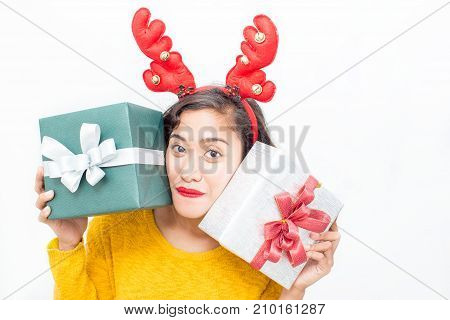 Closeup portrait of playful middle-aged woman wearing toy reindeer horns and holding two gift boxes. Isolated front view on white background.