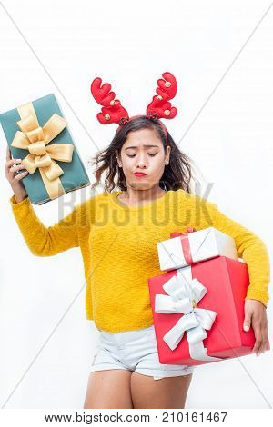 Closeup portrait of doubtful middle-aged woman wearing toy reindeer horns and holding three gift boxes. Isolated front view on white background.