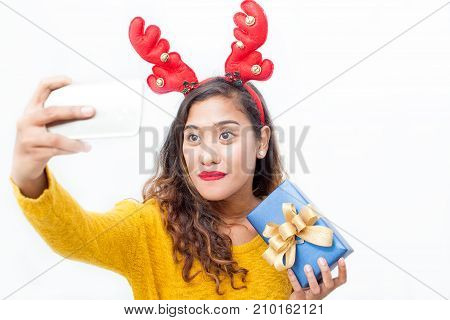 Closeup portrait of content middle-aged woman wearing toy reindeer horns, holding gift box and taking selfie photo on smartphone. Isolated front view on white background.