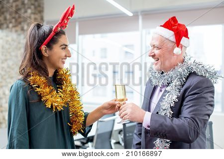 Happy colleagues talking at office party. Cheerful senior executive in Santa hat giving champagne flute to young female employee in antler headband. New Year in office concept