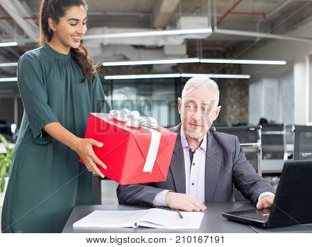 Surprised boss looking at gift from colleague while working on laptop. Cheerful Indian secretary giving big Christmas gift to coworker congratulating him. Unexpected gift concept poster