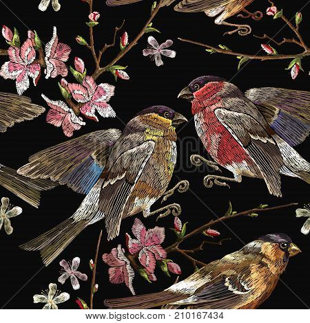 Embroidery birds and blossoming cherry seamless pattern. Classical embroidery bullfinch and titmouse on branch blossoming sakura. Spring fashion pattern template for design of clothes t-shirt design