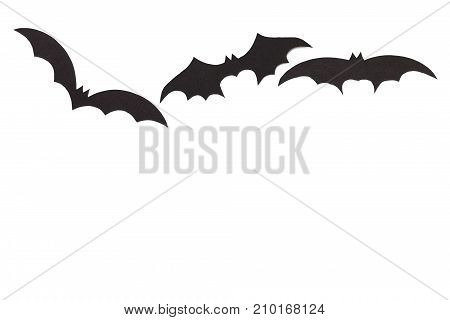 Silhouettes of volatile bats carved out of black paper are isolated on white for Halloween festival poster