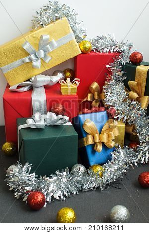 Prepared New Years gifts stacking carelessly in corner. Silver colored tinsel on boxes, Christmas balls splattering on floor. Abundance of presents concept
