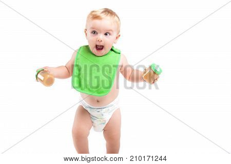 Cute Happy Little Boy In Green Bib Stand With Baby Food