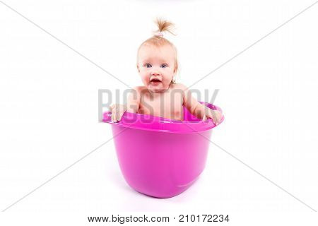 isolated on white cute happy caucasian baby girl with ponytail take bath in purple tub look at camera hands on tub amazed