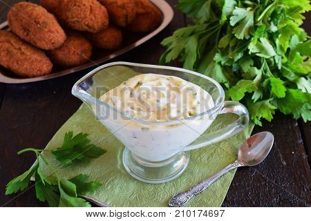 Tartar sauce for fish dishes with yogurt, capers, garlic and lemon, olive oil and sugar in a glass gravy boat on a dark wooden background. Healthy eating concept