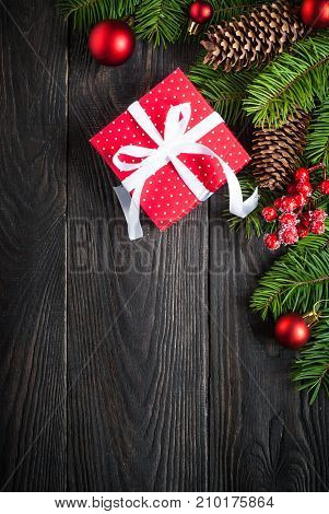Christmas background with fir tree brunch pine cones red balls and red gift box present at dark wooden table. Top view copy space. Vertical.
