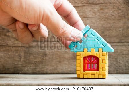 Man hold piece of puzzle to complete the home model object on wood background (Concept of dream home mortgage investment family fulfillment)