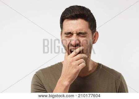 Sleepy Young Man Yawning, Waking Up, Closing His Mouth With Hand, Isolated On Gray Background