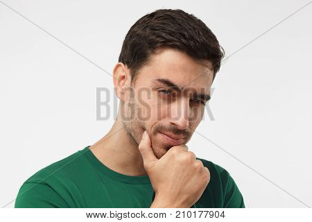 Close Up Portrai Of Suspicious Man In Green T-shirt, Trying To Read Your Thoughts, Isolated On Grey