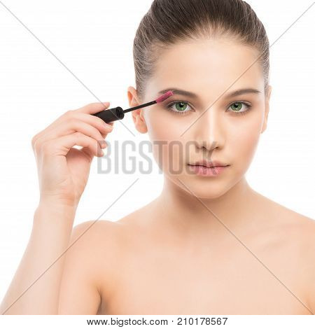 Eye make up apply. Mascara applying closeup, long lashes. Mascara brush. Portrait of beautiful young brunette woman with perfect fresh clean face skin. Eyelashes extensions. Make-up for green eyes. Isolated on a white background.