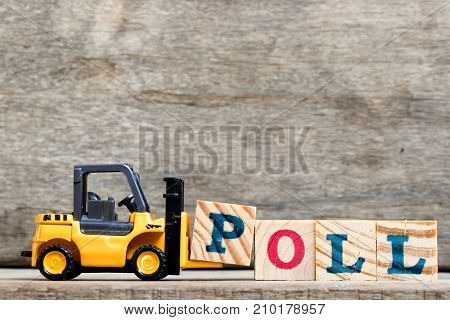 Yellow plastic forklift hold letter P to complete word poll on wood background