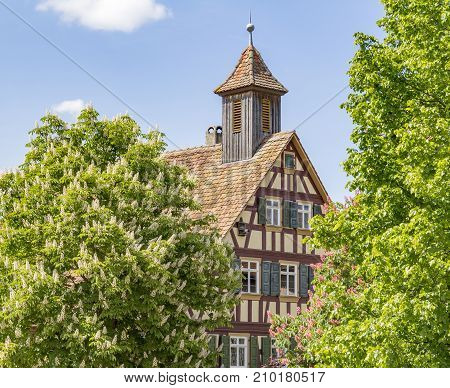 detail of a historic half-timbered house with small bell tower surrounded by trees in suny ambiance