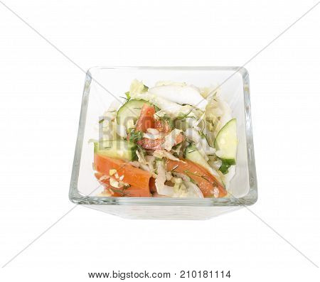 Fresh vegetarian salad in a square glass bowl.  Isolated on a white background.