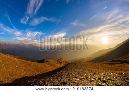 The Italian French Alps At Sunset. Colorful Sky Over The Majestic Mountain Peaks, Dry Barren Terrain