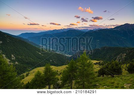 The Italian Alps At Sunset. Summer Colorful Sky Over The Majestic Mountain Peaks, Woodland And Green