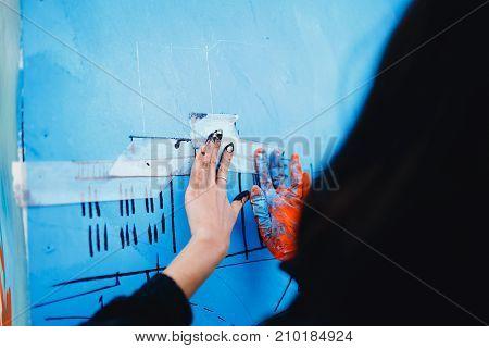 girl prepares a wall for drawing a graffiti drawing