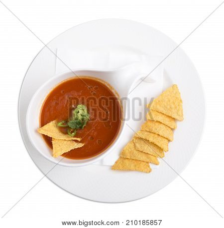 Delicious tomato soup with mint, guacamole and nachos. Isolated on a white background.