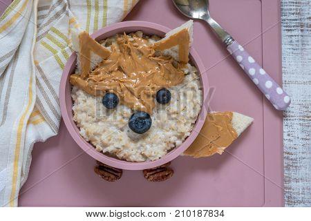Kids breakfast porridge with fruits and nuts look like a fox