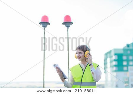 Young Pretty Woman In Green West And Earmuffs Stand On Roof And Hold Tablet